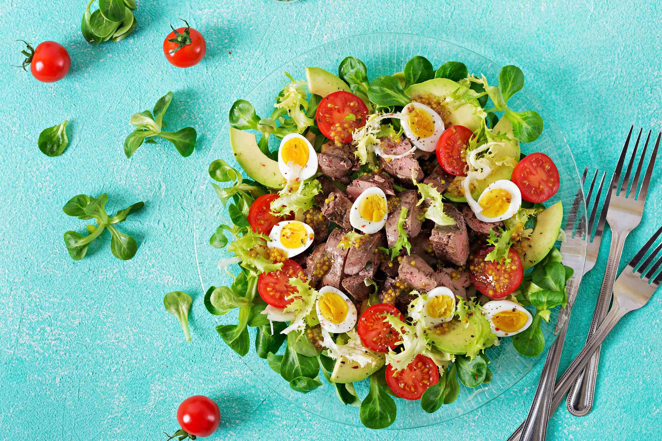 Warm salad from chicken liver, avocado, tomato, and quail eggs
