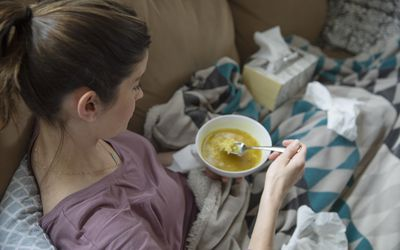 woman with a cold eating soup on couch