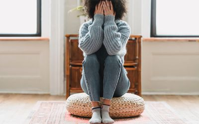 A young Black woman sitting on the floor with her face in her hands.