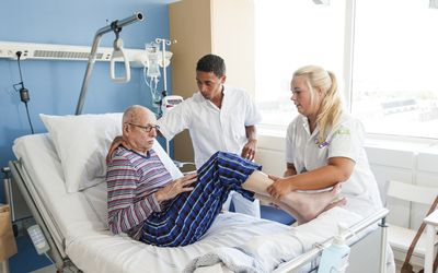 Nurses helping senior man into hospital bed