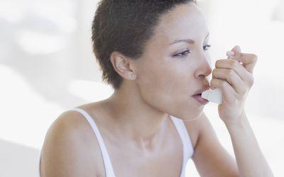 Woman with short hair using an inhaler