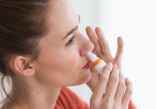 Woman using nasal spray for controlling rhinitis