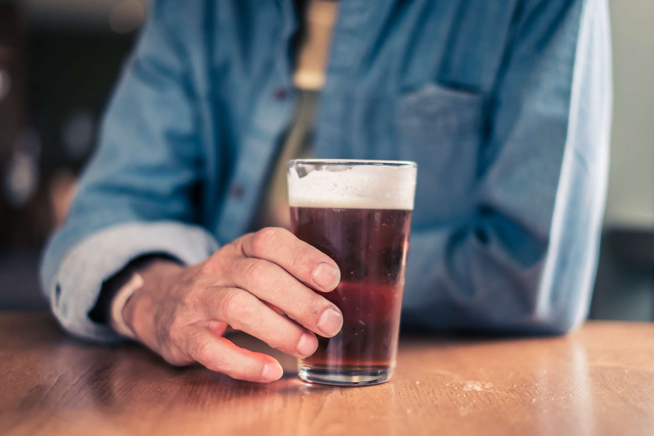 Person at a table holding a glass of beer