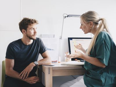 Nurse explaining to young male patient at office in hospital