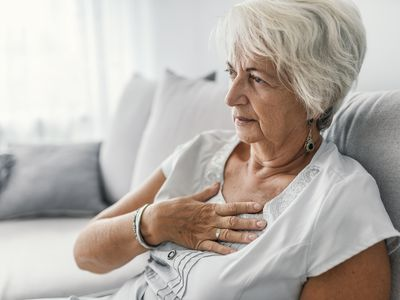 Senior woman suffering from heartburn or chest discomfort symptoms