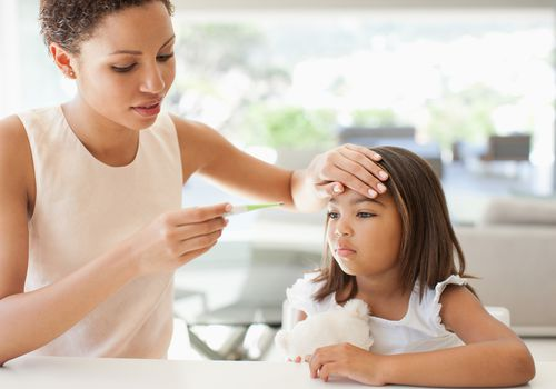 Mother checking daughter's forehead for a fever