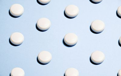 A sequence of round white pills on a light blue background.