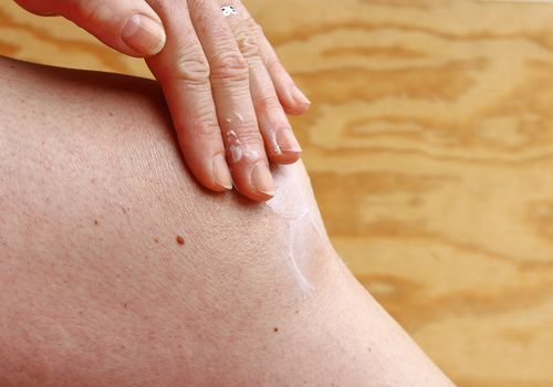 person rubbing ointment on their knee