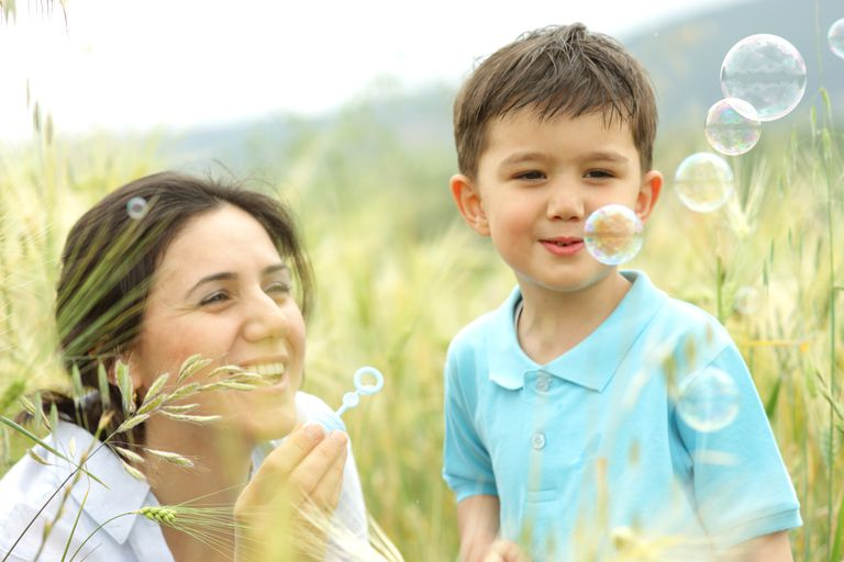 Mother and little boy blowing bubbles in a field