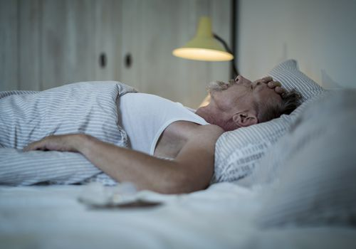 A man laying in bed unable to sleep
