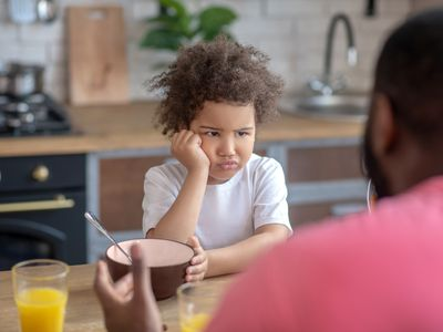 cute little kid looking sad not wanting to eat with dad encouraging to eat
