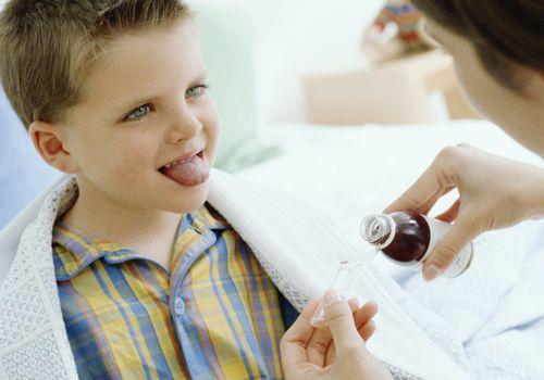 Mother giving son (4-6) medicine
