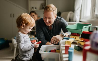 Father plays blocks with his toddler