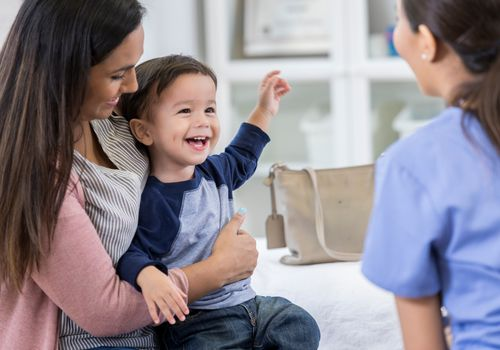 Cheerful toddler boy smiles at pediatrician