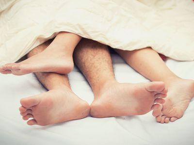heterosexual couple's legs intertwined in bed