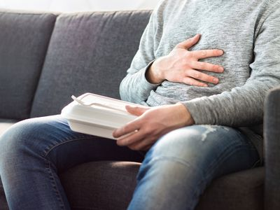 Stomach pain, food poisoning or digestion problem after fast junk food. Man ate too much and is holding belly with hand.