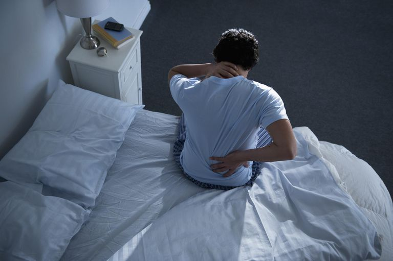 a person in bed holding neck and back