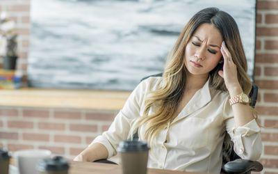 Woman with a headache drinking coffee