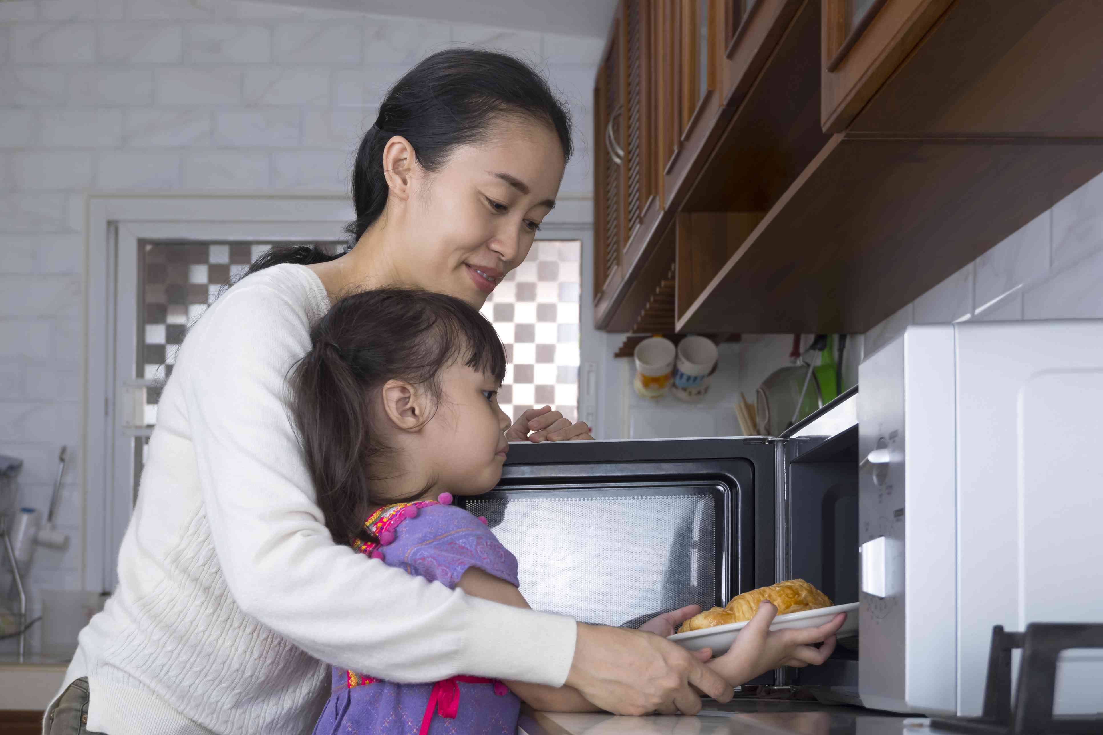 Asian mother and child using a microwave oven