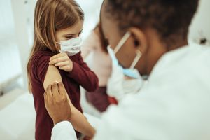 A white female child getting a shot from a Black female healthcare worker; both are wearing face masks.