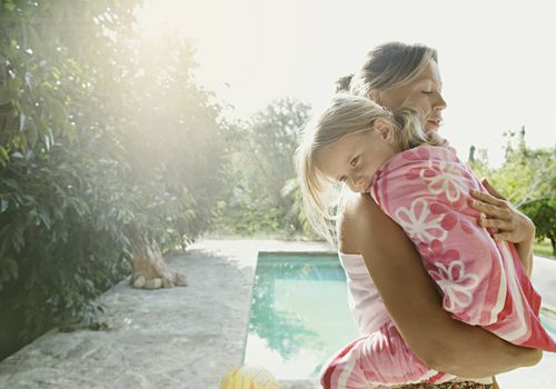 Mother comforting daughter by the pool