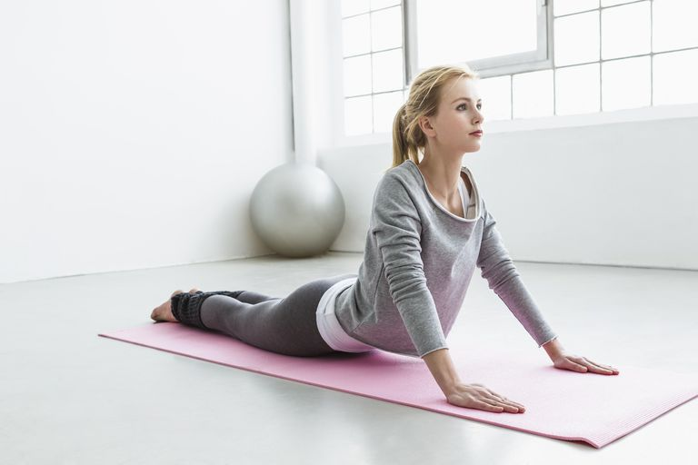 woman on a yoga mat doing upward facing dog pose