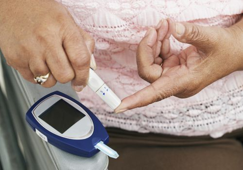 Woman checking blood sugar with a finger prick