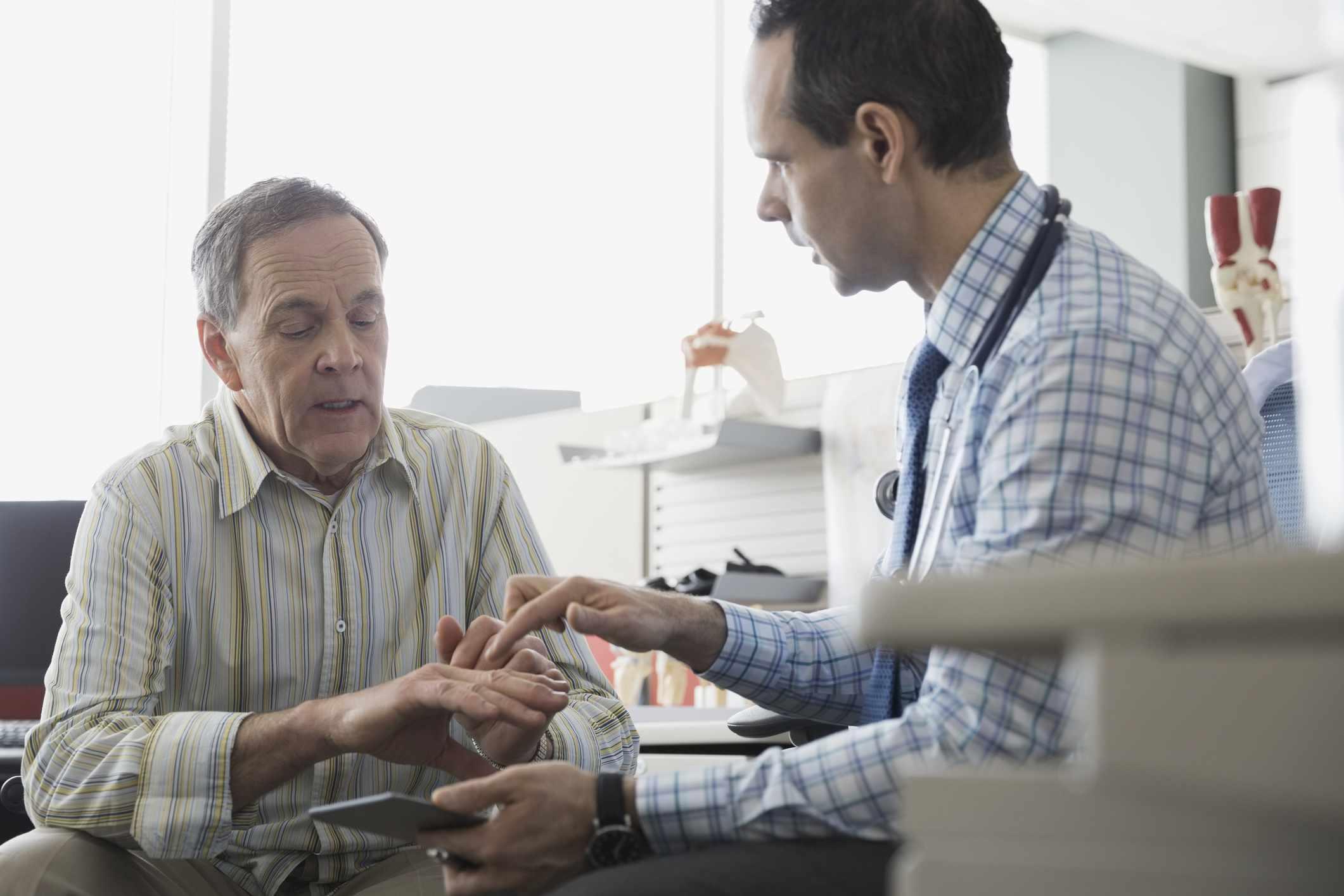 Doctor examining senior patient's hand in office
