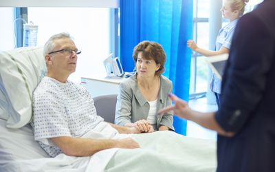 Man sitting in a hospital bed speaking to a nurse