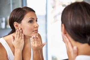 Woman checking her skin in mirror