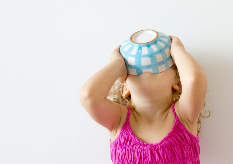 Overeating disease in humans. Girl with head back holding cereal bowl to her mouth