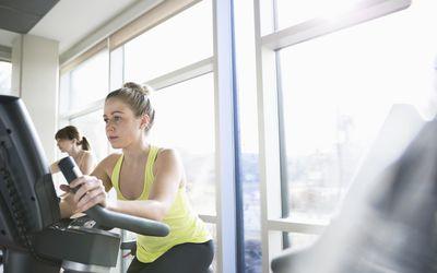 Women exercising on stationary bikes in fitness center