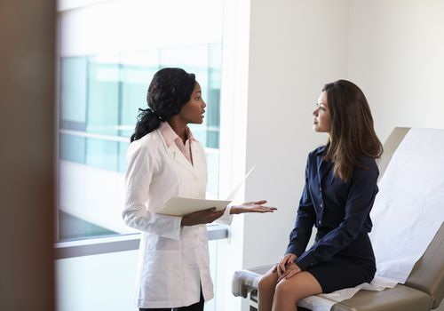 Female Doctor Meeting With Patient In Exam Room