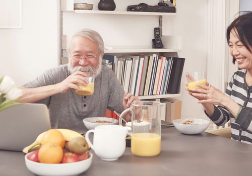 older couple drinking orange juice at breakfast table