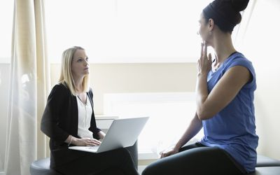 Photo of a woman explaining jaw pain to her physical therapist.