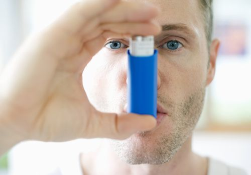 Mid-adult man inhaling asthma inhaler, close-up
