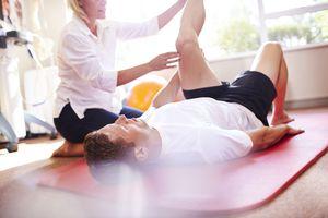 physical therapist stretching man's leg