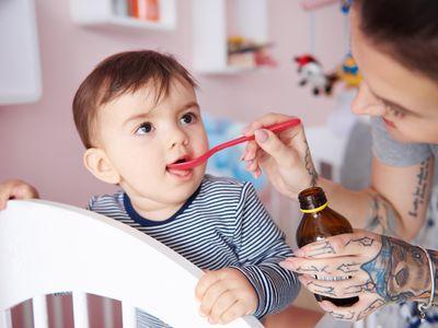 Baby boy drinking medicine off a spoon. Debica, Poland