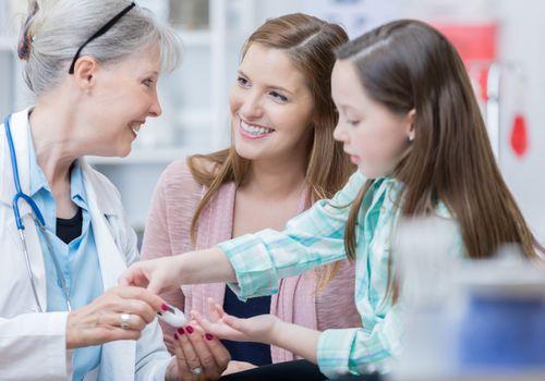 Pediatrician checks young patient's blood sugar levels