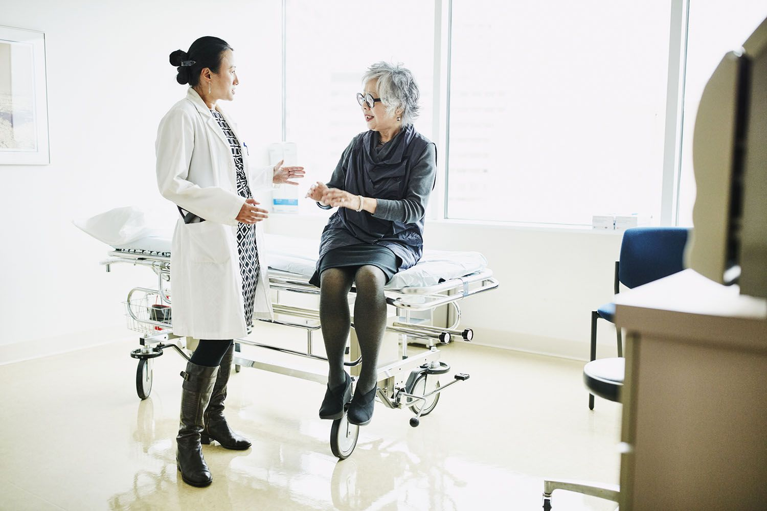 Senior female patient in discussion with doctor during check up in exam room