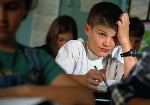 Young student (8-10) sitting at desk with pensive expression.