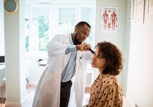male doctor checking female patient's hearing