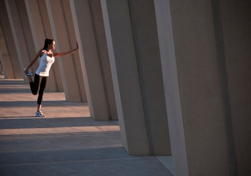 Woman performing standing quad stretch while holding onto concrete wall.