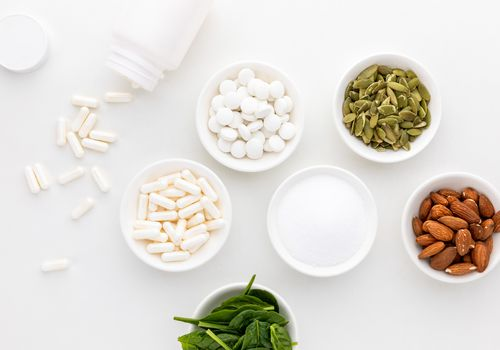 Bowl of spinach, pumpkin seeds, almonds, magnesium tablets, magnesium capsules, and magnesium powder