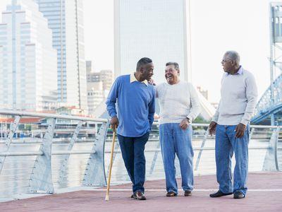 Three senior men laughing, walking on city waterfront