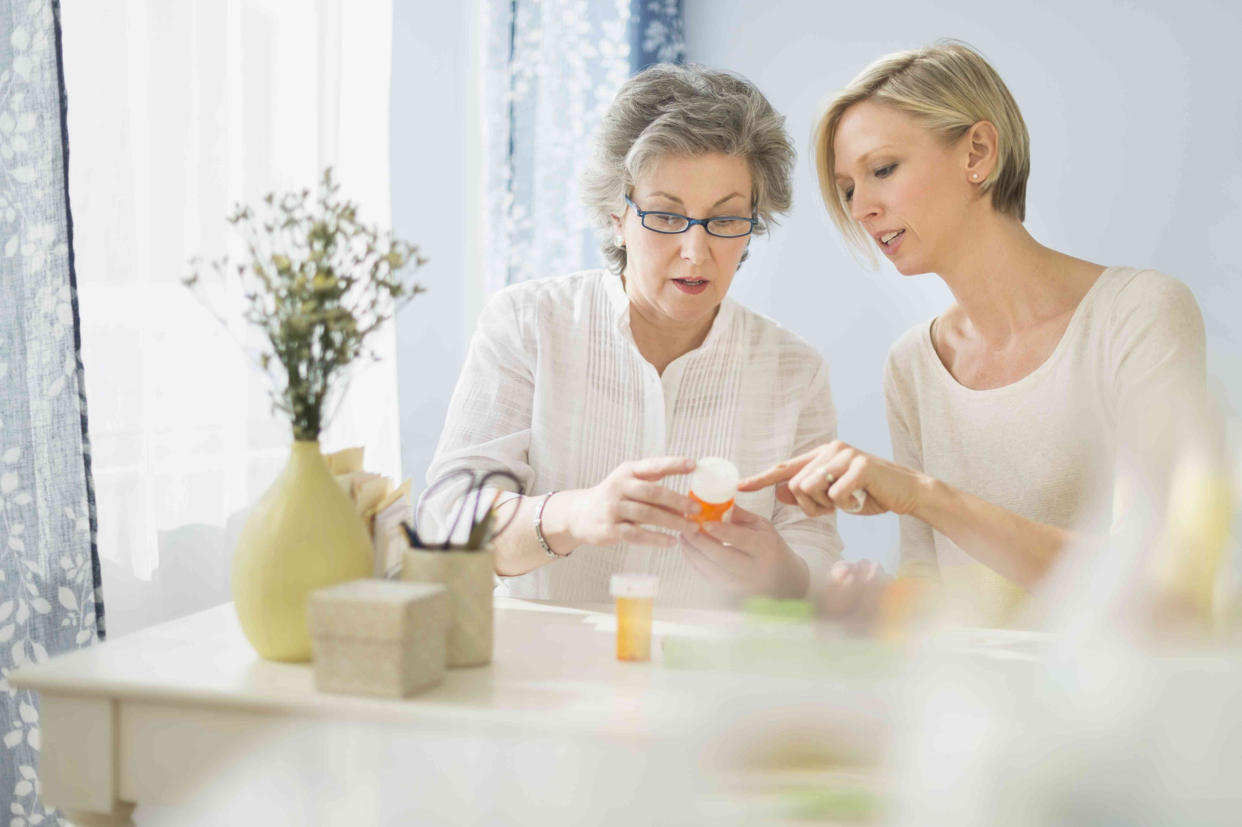 Nurse and mature woman reading labels on medicine bottle, Jersey City, New Jersey, USA