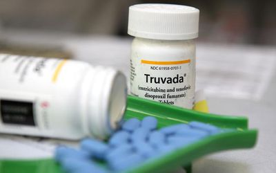 bottle of Truvada with blue pills in front on it