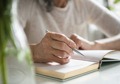 Hands of older woman writing in journal
