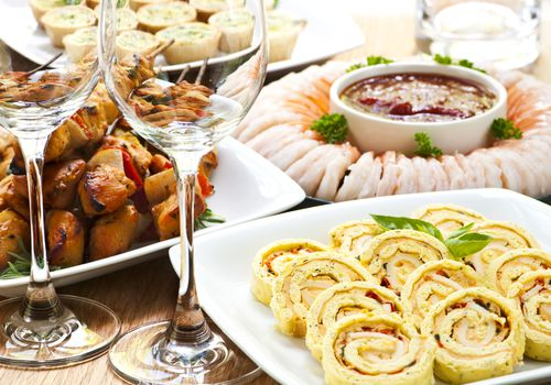plates of appetizers on a table including shrimp, skewers, and sliced wraps