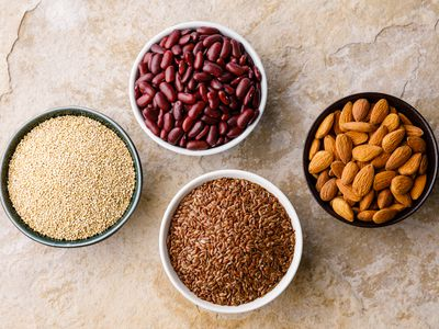 Bowls of beans, nuts, quinoa, and flaxseed
